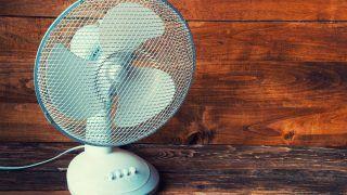 Electric fan on wooden background, copyspace