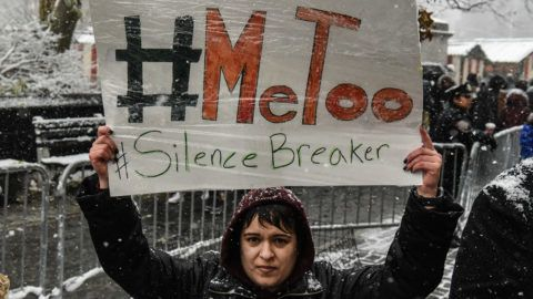 NEW YORK, NY - DECEMBER 09: People carry signs addressing the issue of sexual harassment at a #MeToo rally outside of Trump International Hotel on December 9, 2017 in New York City.   Stephanie Keith/Getty Images/AFP