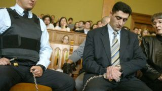 """Accompanied by a police official (L) and an interpretor (R), Azerbaijani army officier Lieutenant Ramil Safarov(C) looks at his watch as the verdict is read 13 April 2006, a convicting him to life imprisonment for hacking to death an Armenian lieutenant while attending a NATO-sponsored training course in Budapest. Judge Andras Vaskuti of the Budapest district court ruled that Ramil Safarov, now 29 and an Azerbaijani army lieutenant, killed Armenian Lieutenant Gurgen Markarian, 26, in """"premeditated, malicious and an unusually cruel"""" way by nearly decapitating him with axe while he slept. Safarov will be eligible for parole in 30 years, according to the ruling.     AFP PHOTO / ATTILA KISBENEDEK / AFP PHOTO / ATTILA KISBENEDEK"""