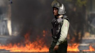 A riot police officer looks on during clashes with anti-government activists in Caracas on July 26, 2017, during a 48-hour general strike called by the opposition. Venezuelans began blocking off deserted streets Wednesday as the opposition launched a 48-hour general strike aimed at thwarting embattled President Nicolas Maduro's controversial plans to rewrite the country's constitution. / AFP PHOTO / Federico PARRA