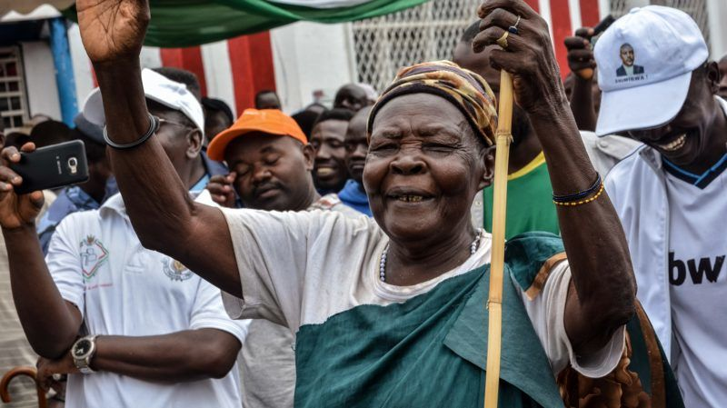 """An elderly woman reacts as Burundians take to the streets to celebrate Burundi's withdrawal from the International Criminal Court (ICC) in Bujumbura, Brundi, on October 28, 2017.  Thousands of Burundians on October 28 answered the government's call to celebrate the country's withdrawal from the International Criminal Court, cheering the """"historic"""" day using slogans such as """"bye bye ICC"""". Burundi on October 27 became the first ever nation to leave the ICC, set up some 15 years ago to prosecute those behind the world's worst atrocities.  / AFP PHOTO / STR"""