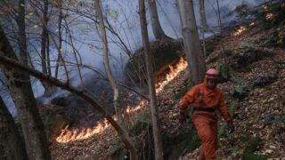 Firefighters volunteers work against fires near Ribordone, northern Turin, on October 30, 2017. Firefighters are still battling today against the wildfires that have hit the northern region of Piedmont. / AFP PHOTO / Marco BERTORELLO