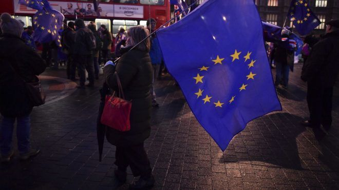 """Pro-EU protesters wave EU and Union Flags outside the Houses of Parliament in central London on December 11, 2017 as Britain's Prime Minister Theresa May makes a statement to the House on the phase one Brexit interim agreement with the EU and takes questions from lawmakers. British Prime Minister Theresa May will tell lawmakers Monday there is a """"new sense of optimism"""" around Brexit talks, despite a spat with Ireland over last week's interim deal with the EU. Before her statement in the House of Commons, May chaired a meeting of her cabinet ministers, many of whom are divided on the shape of Britain's exit from the European Union.  / AFP PHOTO / Ben STANSALL"""