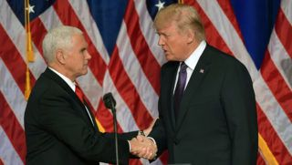 """US President Donald Trump shakes hands with US Vice president Mike pence as he arrives to speak on his national security strategy at the Ronald Reagan Building in Washington, DC on December 18, 2017. President Donald Trump rolled out his first """"National Security Strategy"""", a combative document designed to put meat on the bones of his """"America First"""" sloganeering. / AFP PHOTO / MANDEL NGAN"""