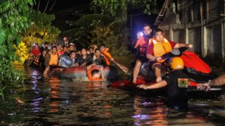 Rescue workers evacuate flood-affected residents in Davao on the southern Philippine island of Mindanao early on December 23, 2017, after Tropical Storm Tembin dumped torrential rains across the island. The death toll from the tropical storm that struck the southern Philippines has risen to 30 with five others missing, officials said on December 23. / AFP PHOTO / MANMAN DEJETO