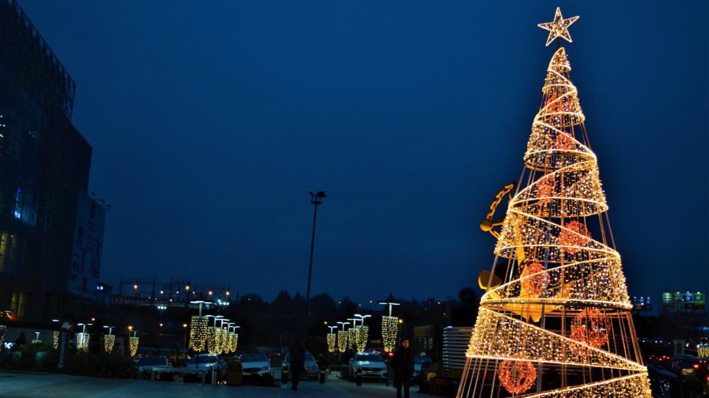 A man looks at an illuminated decoration in the shape of a Christmas tree outside a shopping mall in Ankara, Turkey on December 22, 2017. (Photo by Altan Gocher/NurPhoto)