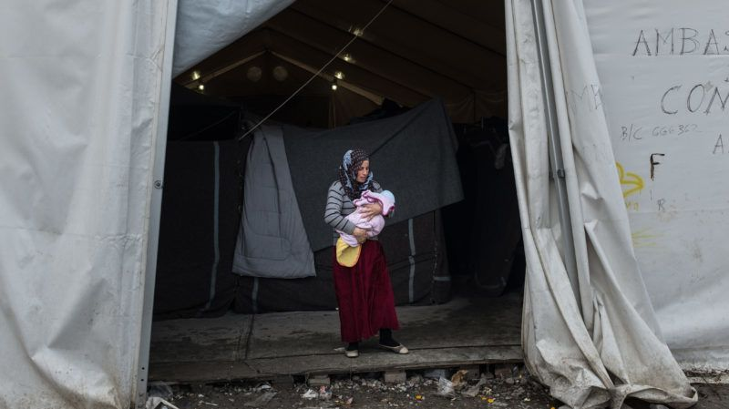 A woman holding a baby stands at the entrance of a tent, inside the Moria camp on the island of Lesbos, Greece, on November 28, 2017. Nick Paleologos / SOOC