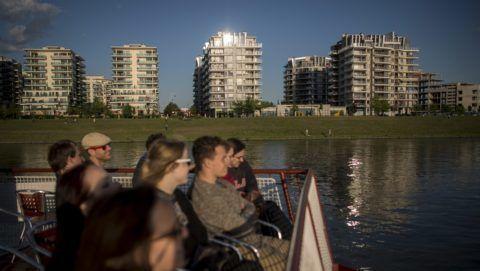 Budapest, 2015. május 11. Turisták a BKK hajóján utaznak a Duna fõvárosi szakaszán, háttérben a Marina Part lakópark házai 2015. május 11-én. A Duna Védelmi Nemzetközi Bizottság 2004-ben létrejött kezdeményezésére a Duna menti országok június 29-én ünneplik a Nemzetközi Duna Napot, amelynek célja, hogy felhívja a figyelmet Európa második leghosszabb folyójának értékeire és megóvására. MTI Fotó: Kallos Bea