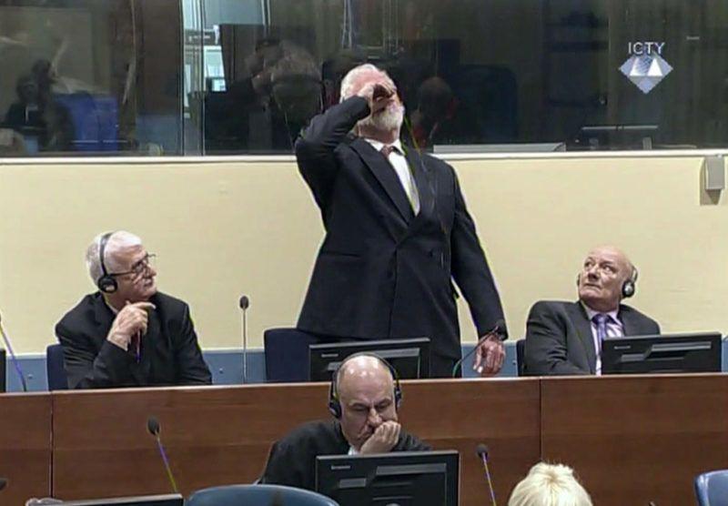 Hága, 2017. november 29.A Nemzetközi Törvényszék általk özreadott képen a muzulmánok ellen elkövetett etnikai tisztogatással vádolt Slobodan Praljak nyugalmazott tábornok, a horvát védelmi minisztérium volt helyettes vezetője iszik valamit fellebbviteli ítélethirdetésén az egykori Jugoszlávia területén elkövetett háborús bűnöket vizsgáló hágai Nemzetközi Törvényszék tárgyalótermében 2017. november 29-én. Az ítélethirdetést felfüggesztették, mert Praljak azt kiabálta, hogy nem háborús bűnös és kijelentette, hogy mérget ivott, amikor meghallotta, hogy a törvényszék helyben hagyta 20 éves börtönbüntetését. A Praljak és öt másik egykori boszniai horvát vezető fellebbezésében hozott ítélettel lezárul az ENSZ-törvényszék utolsó pere. Balra Bruno Stojic volt horvát katonai vezető, jobbra Milivoj Petkovic volt horvát vezérezredes.(MTI/AP/Nemzetközi Törvényszék)