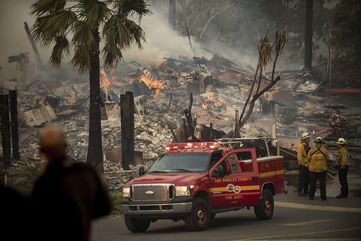 Ventura megye, 2017. december 5.Tűzoltók a kaliforniai Ventura megyében pusztító erdőtűzben leégett lakóépületek egyikénél 2017. december 5-én. Fél nap alatt több mint 12 ezer hektár vált a lángok martalékává és 25 ezer embernek kellett elhagynia az otthonát. (MTI/AP/Noah Berger)