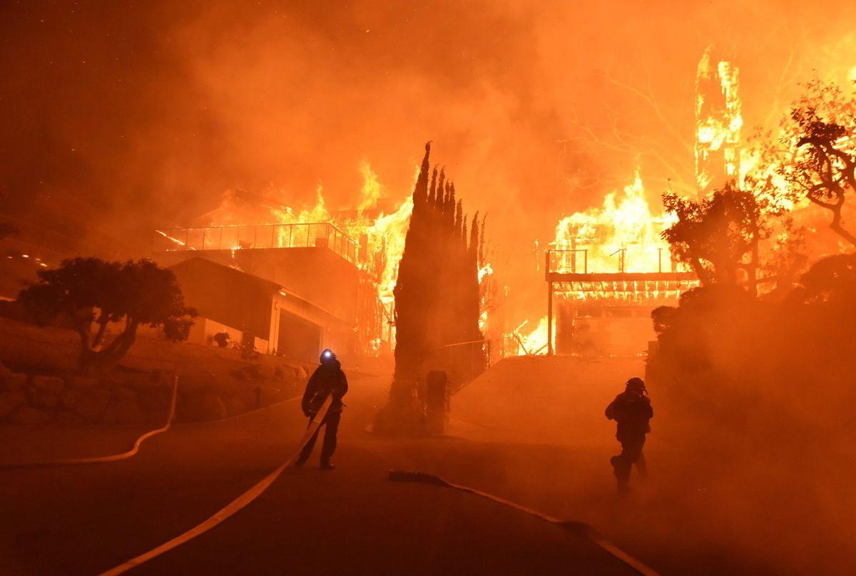 Ventura megye, 2017. december 5.A Ventura megyei tűzoltóság által közreadott képen lángoló lakóházakat locsolnak tűzoltók a kaliforniai megyében pusztító erdőtűz idején, 2017. december 5-én. Fél nap alatt több mint 12 ezer hektár vált a lángok martalékává és 25 ezer embernek kellett elhagynia az otthonát. (MTI/AP/Ventura megyei tűzoltóság/Ryan Cullom)