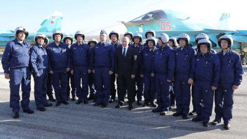Hmejmími légitámaszpont, 2017. december 11.Vlagyimir Putyin orosz elnök (k) pilótákkal fényképezkedik a szíriai Hmejmímnél működő orosz légitámaszponton 2017. december 11-én. Putyin a bázison tett villámlátogatásán elrendelte az orosz csapatok Szíriából történő visszavonásának megkezdését. (MTI/AP/Szputnyik/Kreml pool/Mihail Klimentyev)