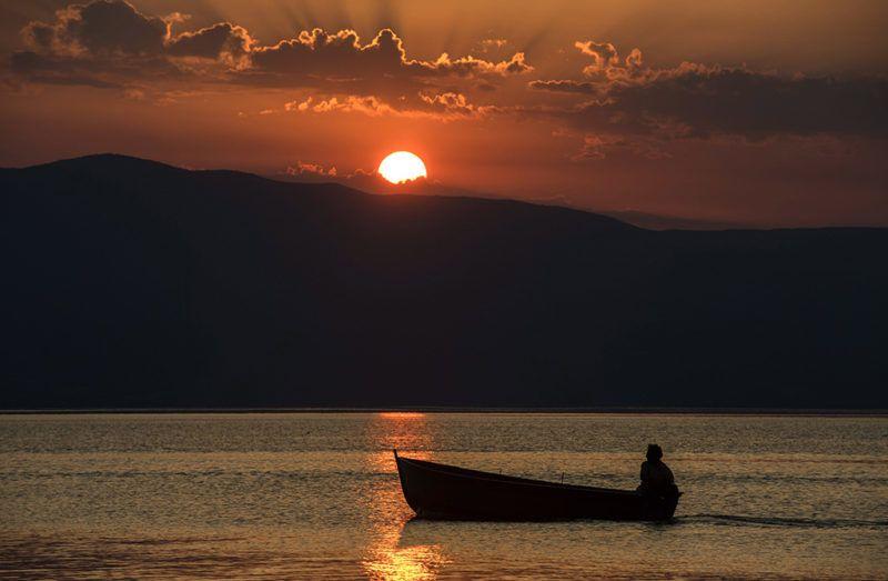 Trpejca, 2017. augusztus 3.Egy férfi csónakjából nézi a naplementét az Ohrid-tavon, a macedóniai Trpejca falu közelében 2017. augusztus 3-án. A délszláv államban másodfokú hőségriasztás van érvényben. (MTI/EPA/Georgi Licovszki)