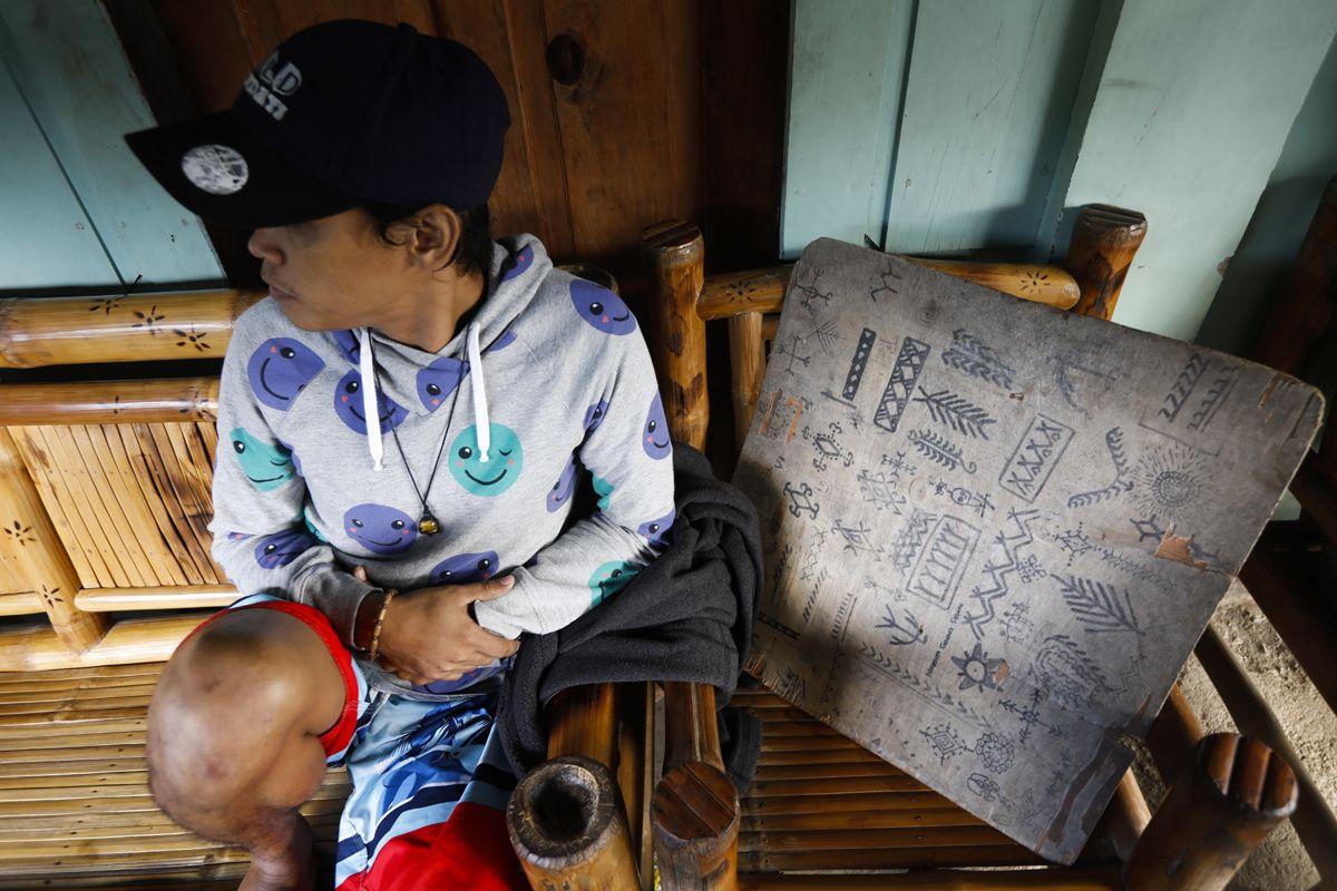 """Buscalan, 2017. december 1.Turista várja Whang-od Fülöp-szigeteki tetoválóművészt a műhelyében, a Manilától mintegy 400 kilométerre, északra fekvő hegyi faluban, Buscanban 2017. november 29-én. Az ősi kalinga törzshöz tartozó """"mambabatok"""", azaz tetoválóművész korát 94 és 99 év közöttire teszik. Whang-od a mai napig szénport és a pomela gyümölcsfa tüskéit használja munkái elkészítéséhez. Munkássága és az ősi hagyományok ápolása miatt a nemzet művésze kitüntetésre is várományos. (MTI/EPA/Rolex Dela Pena)"""