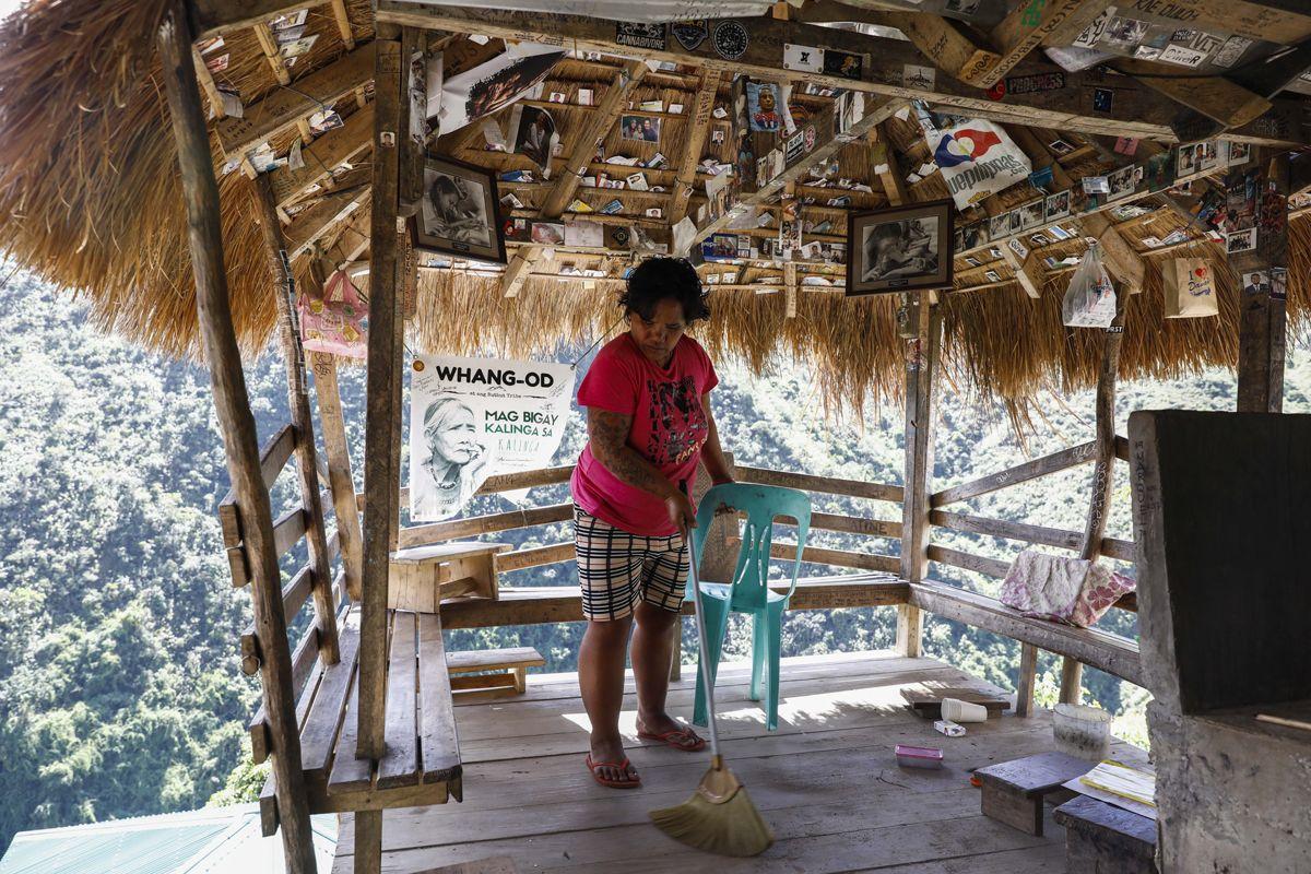 """Buscalan, 2017. december 1.Aboc Palicas, Whang-od Fülöp-szigeteki tetoválóművész unokahúga takarítja nagynénje műhelyét a Manilától mintegy 400 kilométerre északra fekvő hegyi faluban, Buscanban 2017. november 29-én. Az ősi kalinga törzshöz tartozó """"mambabatok"""", azaz tetoválóművész korát 94 és 99 év közöttire teszik. Whang-od a mai napig szénport és a pomela gyümölcsfa tüskéit használja munkái elkészítéséhez. Munkássága és az ősi hagyományok ápolása miatt a nemzet művésze kitüntetésre is várományos. (MTI/EPA/Rolex Dela Pena)"""