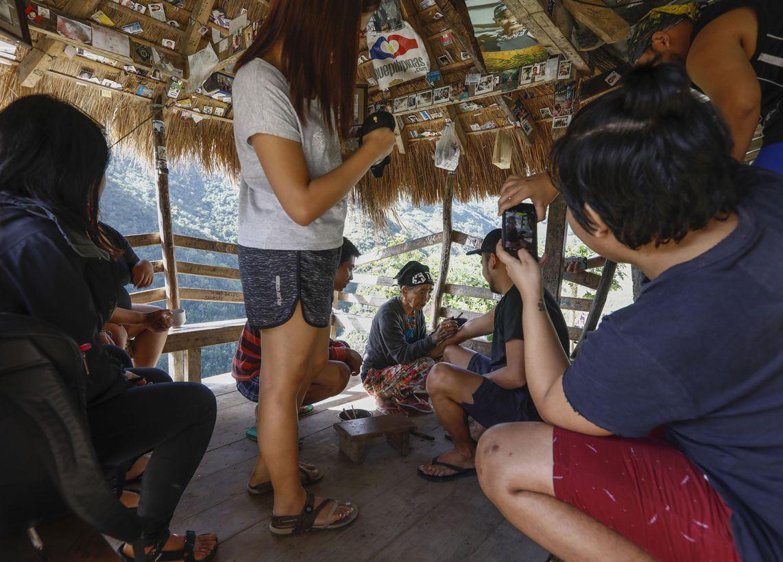 """Buscalan, 2017. december 1.Whang-od Fülöp-szigeteki tetoválóművész egy férfi karját tetoválja busculani otthonában, a Manilától mintegy 400 kilométerre északra fekvő hegyi faluban 2017. november 29-én. Az ősi kalinga törzshöz tartozó """"mambabatok"""", azaz tetoválóművész korát 94 és 99 év közöttire teszik. Whang-od a mai napig szénport és a pomela gyümölcsfa tüskéit használja munkái elkészítéséhez. Munkássága és az ősi hagyományok ápolása miatt a nemzet művésze kitüntetésre is várományos. (MTI/EPA/Rolex Dela Pena)"""