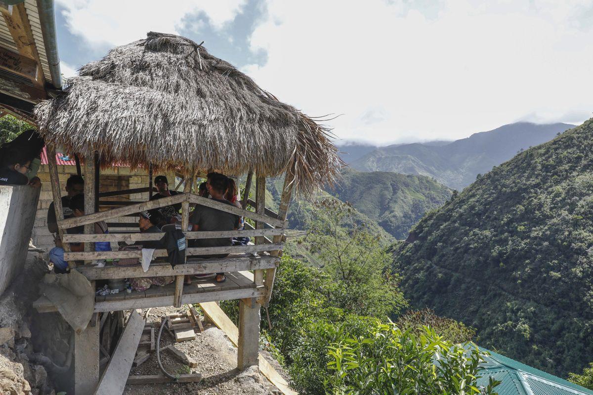 """Buscalan, 2017. december 1.Turisták várják Whang-od Fülöp-szigeteki tetoválóművészt a műhelyében, a Manilától mintegy 400 kilométerre, északra fekvő hegyi faluban, Buscanban 2017. november 29-én. Az ősi kalinga törzshöz tartozó """"mambabatok"""", azaz tetoválóművész korát 94 és 99 év közöttire teszik. Whang-od a mai napig szénport és a pomela gyümölcsfa tüskéit használja munkái elkészítéséhez. Munkássága és az ősi hagyományok ápolása miatt a nemzet művésze kitüntetésre is várományos. (MTI/EPA/Rolex Dela Pena)"""