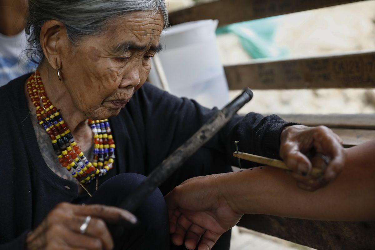 """Buscalan, 2017. december 1.Whang-od Fülöp-szigeteki tetoválóművész egy nő alkarjára tetoválja a három pontból álló egyedi ismertetőjelét busculani otthonában, a Manilától mintegy 400 kilométerre északra fekvő hegyi faluban 2017. november 28-án. Az ősi kalinga törzshöz tartozó """"mambabatok"""", azaz tetoválóművész korát 94 és 99 év közöttire teszik. Whang-od a mai napig szénport és a pomela gyümölcsfa tüskéit használja munkái elkészítéséhez. Munkássága és az ősi hagyományok ápolása miatt a nemzet művésze kitüntetésre is várományos. (MTI/EPA/Rolex Dela Pena)"""