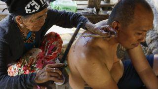 """Buscalan, 2017. december 1.Whang-od Fülöp-szigeteki tetoválóművész egy férfi hátát tetoválja busculani otthonában, a Manilától mintegy 400 kilométerre északra fekvő hegyi faluban 2017. november 29-én. Az ősi kalinga törzshöz tartozó """"mambabatok"""", azaz tetoválóművész korát 94 és 99 év közöttire teszik. Whang-od a mai napig szénport és a pomela gyümölcsfa tüskéit használja munkái elkészítéséhez. Munkássága és az ősi hagyományok ápolása miatt a nemzet művésze kitüntetésre is várományos. (MTI/EPA/Rolex Dela Pena)"""