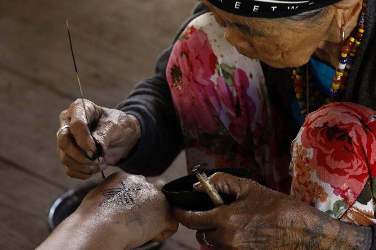 """Buscalan, 2017. december 1.Whang-od Fülöp-szigeteki tetoválóművész egy férfi kézfejét tetoválja busculani otthonában, a Manilától mintegy 400 kilométerre északra fekvő hegyi faluban 2017. november 29-én. Az ősi kalinga törzshöz tartozó """"mambabatok"""", azaz tetoválóművész korát 94 és 99 év közöttire teszik. Whang-od a mai napig szénport és a pomela gyümölcsfa tüskéit használja munkái elkészítéséhez. Munkássága és az ősi hagyományok ápolása miatt a nemzet művésze kitüntetésre is várományos. (MTI/EPA/Rolex Dela Pena)"""