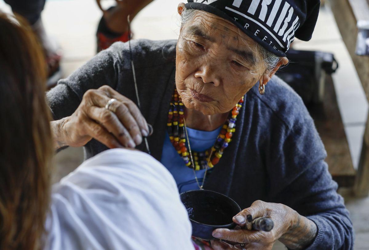 """Buscalan, 2017. december 1.Whang-od Fülöp-szigeteki tetoválóművész egy nő vállát tetoválja busculani otthonában, a Manilától mintegy 400 kilométerre északra fekvő hegyi faluban 2017. november 29-én. Az ősi kalinga törzshöz tartozó """"mambabatok"""", azaz tetoválóművész korát 94 és 99 év közöttire teszik. Whang-od a mai napig szénport és a pomela gyümölcsfa tüskéit használja munkái elkészítéséhez. Munkássága és az ősi hagyományok ápolása miatt a nemzet művésze kitüntetésre is várományos. (MTI/EPA/Rolex Dela Pena)"""