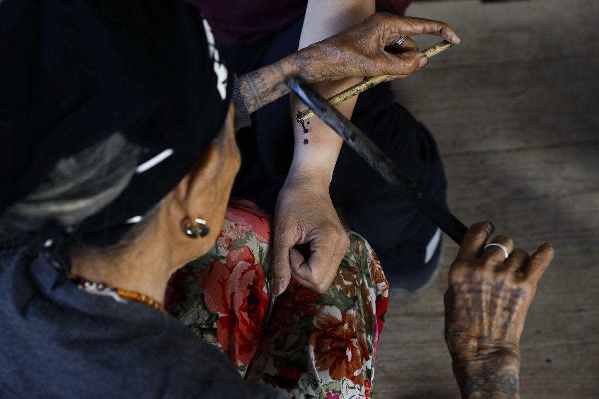 """Buscalan, 2017. december 1.Whang-od Fülöp-szigeteki tetoválóművész egy nő alkarjára tetoválja a három pontból álló egyedi ismertetőjelét busculani otthonában, a Manilától mintegy 400 kilométerre északra fekvő hegyi faluban 2017. november 29-én. Az ősi kalinga törzshöz tartozó """"mambabatok"""", azaz tetoválóművész korát 94 és 99 év közöttire teszik. Whang-od a mai napig szénport és a pomela gyümölcsfa tüskéit használja munkái elkészítéséhez. Munkássága és az ősi hagyományok ápolása miatt a nemzet művésze kitüntetésre is várományos. (MTI/EPA/Rolex Dela Pena)"""