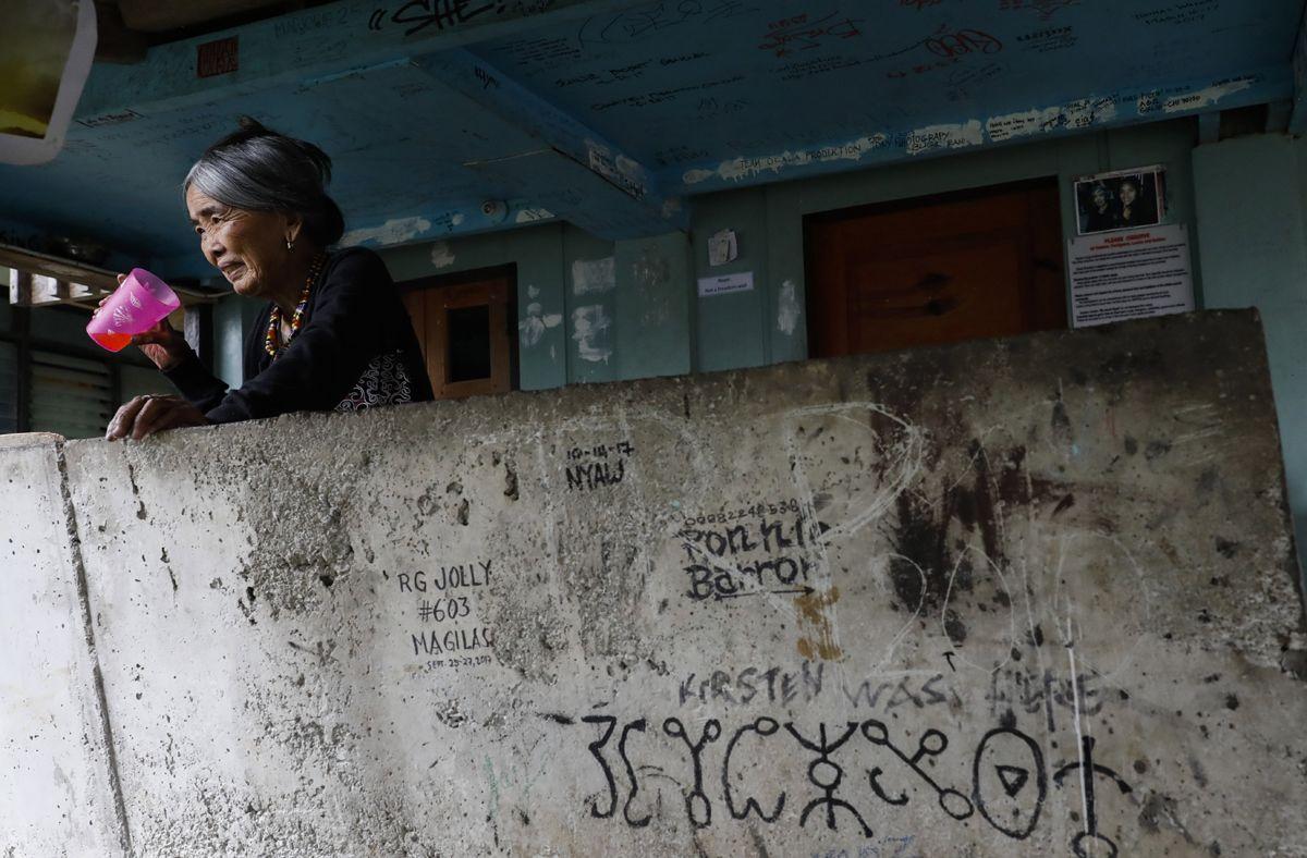 """Buscalan, 2017. december 1.Whang-od Fülöp-szigeteki tetoválóművész iszik a Manilától mintegy 400 kilométerre, északra fekvő hegyi faluban, Buscanban lévő otthonában 2017. november 28-án. Az ősi kalinga törzshöz tartozó """"mambabatok"""", azaz tetoválóművész korát 94 és 99 év közöttire teszik. Whang-od a mai napig szénport és a pomela gyümölcsfa tüskéit használja munkái elkészítéséhez. Munkássága és az ősi hagyományok ápolása miatt a nemzet művésze kitüntetésre is várományos. (MTI/EPA/Rolex Dela Pena)"""