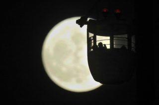 Tokió, 2017. december 3. Egy tokiói vidámpark gondolája a közeli telihold, az úgynevezett szuperhold elõtt 2017. december 3-án. A szuperhold kifejezés az ellipszis alakú holdpálya Földhöz legközelebbi pontján bekövetkezõ telihold fázist jelöli, amikor az égitest a pályájának legtávolabbi pontjához képest nagyjából ötvenezer kilométerrel közelebb van a Földhöz, ezért az átlagosnál mintegy 14 százalékkal nagyobbnak látszik. (MTI/EPA/Majama Kimimasza)
