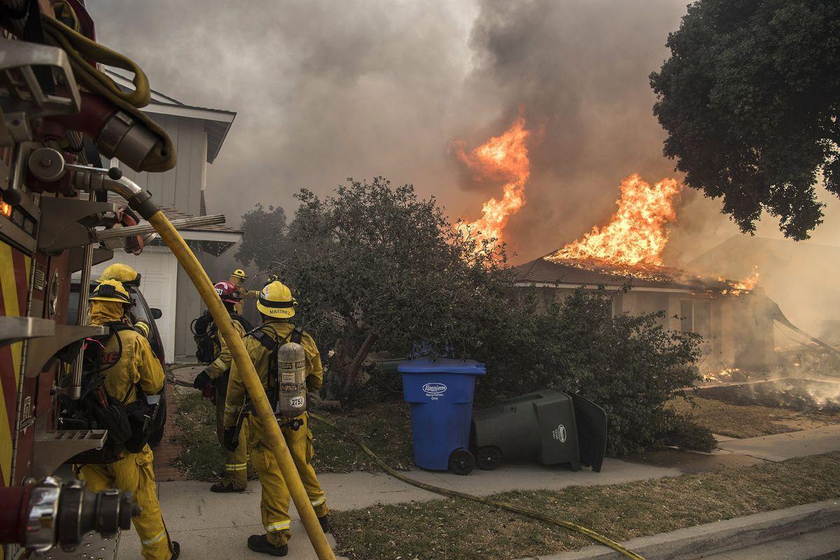 Ventura, 2017. december 6.Tűzoltók egy lángoló háznál a kaliforniai Ventura megyében pusztító erdőtűz idején, 2017. december 5-én. Eddig több mint 18 ezer hektár vált a lángok martalékává és 27 ezer embernek kellett elhagynia az otthonát. (MTI/EPA/John Cetrino)