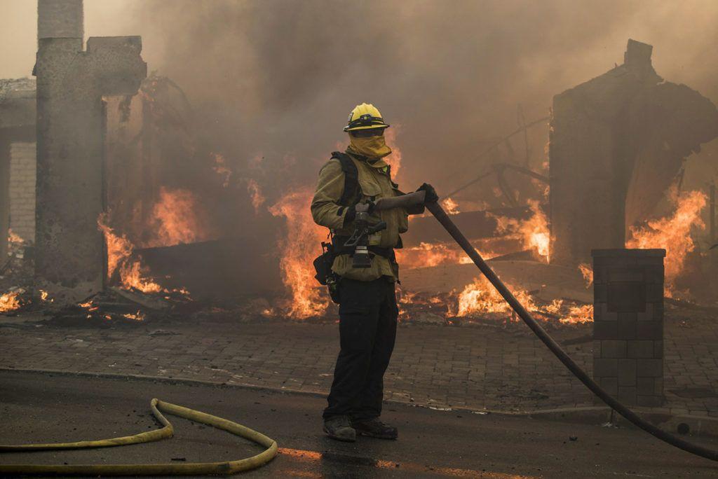 Ventura, 2017. december 6.Tűzoltó egy lángoló háznál a kaliforniai Ventura megyében pusztító erdőtűz idején, 2017. december 5-én. Eddig több mint 18 ezer hektár vált a lángok martalékává és 27 ezer embernek kellett elhagynia az otthonát. (MTI/EPA/John Cetrino)