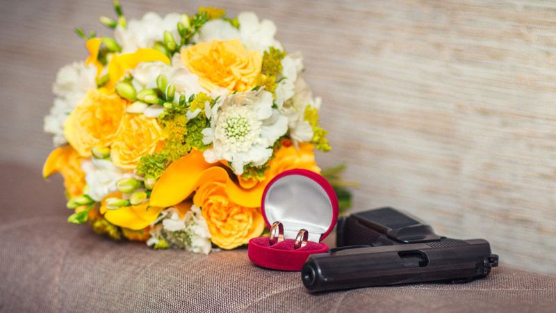 Wedding in mafia style. Composition of gun, wedding rings and bouquet