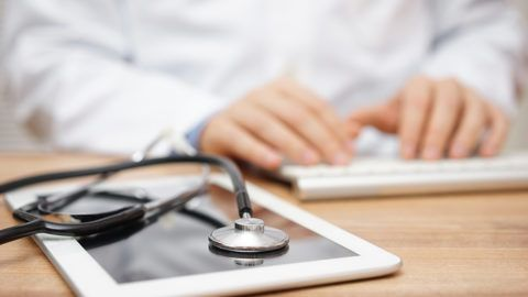 Blurred doctor in background typing on computer keyboard with tablet and stethoscope in foreground