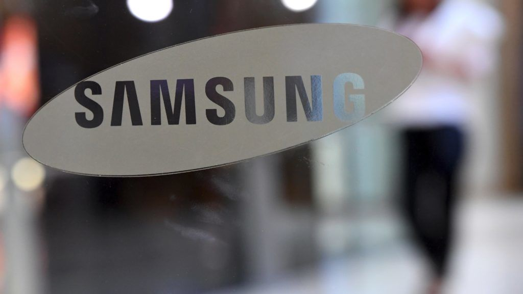 A woman walks past the logo of Samsung at the company's showroom in Seoul on July 7, 2017. Samsung Electronics expects profits to soar 72 percent in the second quarter to a record high, it said on July 7, as it moves on from a recall debacle thanks to rising memory chip prices and increased demand for smartphones. / AFP PHOTO / JUNG Yeon-Je