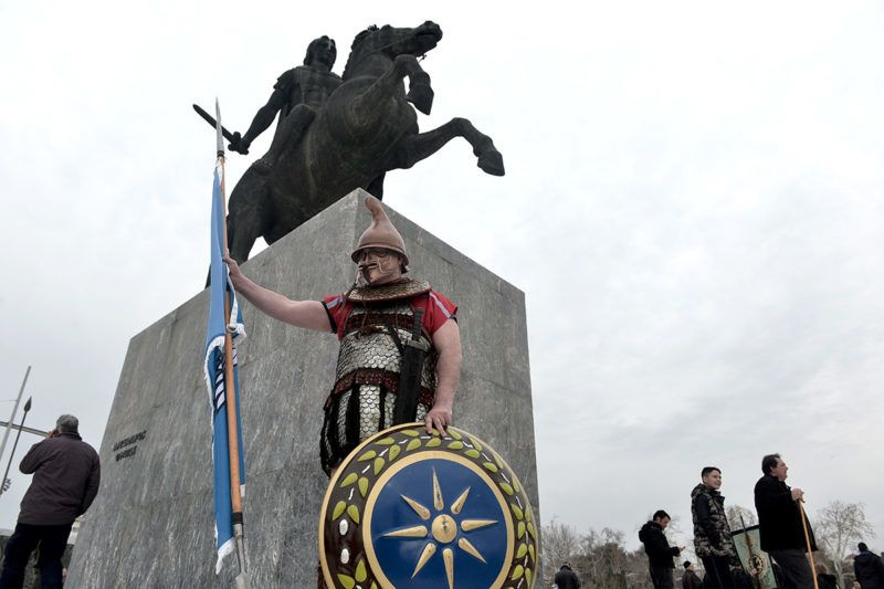 A man dress as ancien Greek pose at the foot of a statue of Alexander the Great as people start to gather prior to a protest against the use of the name Macedonia following the developments on the issue with the neighbour country, in Thessaloniki on January 21, 2018.Thousands of people are expected to take to the streets of northern Greece's biggest city Thessaloniki on January 21, 2018 as hardliners seek to block any deal in the long-running name dispute between Athens and Skopje that contains the term Macedonia. Athens argues that the name Macedonia suggests that Skopje has territorial claims to the northern Greek region of the same name, of which Thessaloniki is the capital. / AFP PHOTO / SAKIS MITROLIDIS