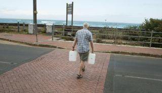 A man walks across the road with two water tanks after collect drinking water from pipes fed by an underground spring, in St. James, about 25km from the city centre, on January 19, 2018, in Cape Town. Cape Town will next month slash its individual daily water consumption limit by 40 percent to 50 litres, the mayor said on January 18, as the city battles its worst drought in a century. / AFP PHOTO / RODGER BOSCH