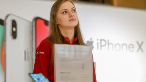 A girl stays near the Apple promoting table at one of shopping malls in Kyiv, Ukraine, Dec.12, 2017. iPhone X official sales started in Ukraine. (Photo by Sergii Kharchenko/NurPhoto)
