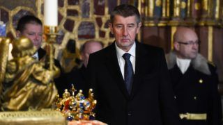 Czech Prime Minister Andrej Babis looks at the Crown of Saint Wenceslas of Bohemia before the opening of the 'Czech Jewels' exhibition on January 15, 2018, at the Prague Castle in the Czech capital. The crown, named after the Duke and Patron Saint Wenceslas I of the Premyslids dynasty of Bohemia, has an unusual design, with vertical fleurs-de-lis standing at the front, back and sides. Made of gold and precious stones for King Charles IV in 1347, it weights 2.475kg. Since 1867 it has been stored in the St. Vitus Cathedral of the Prague Castle. The jewels have always played an important role as a symbol of Bohemian statehood. / AFP PHOTO / Michal Cizek
