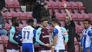 West Ham United's French defender Arthur Masuaku (L) is shown a red card by referee Chris Kavanagh during the English FA Cup fourth round football match between Wigan Athletic and West Ham United at the DW Stadium in Wigan, northwest England, on January 27, 2018. / AFP PHOTO / Oli SCARFF / RESTRICTED TO EDITORIAL USE. No use with unauthorized audio, video, data, fixture lists, club/league logos or 'live' services. Online in-match use limited to 75 images, no video emulation. No use in betting, games or single club/league/player publications.  /