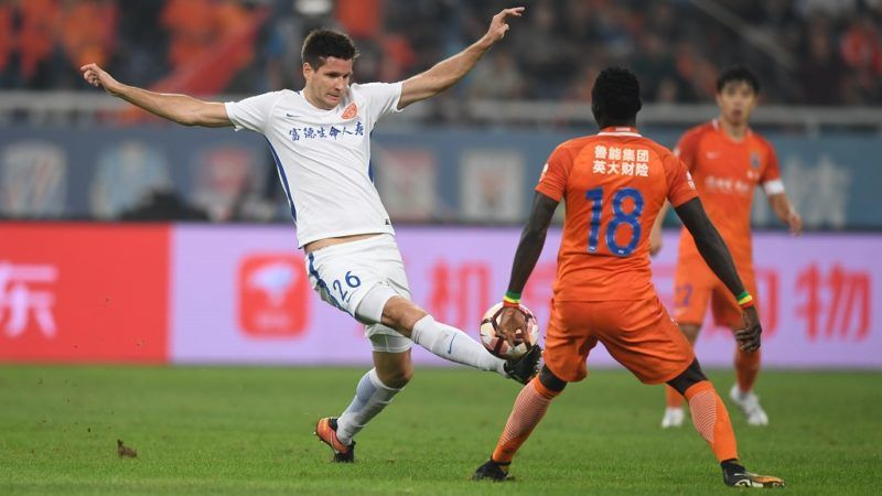 Hungarian football player Richard Guzmics, left, of Yanbian Funde, challenges Senegalese football player Papiss Cisse of Shandong Luneng Taishan in their 25th round match during the 2017 Chinese Football Association Super League (CSL) in Ji'nan city, east China's Shandong province, 16 September 2017.  Shandong Luneng played draw to Yanbian Funde 1-1.