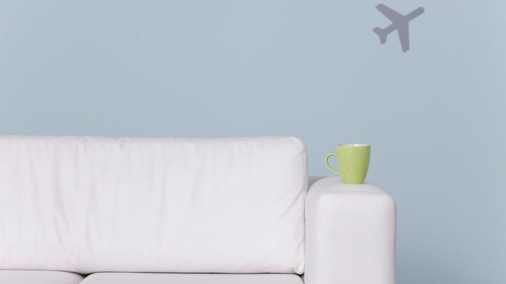 Mug on arm of sofa, airplane shape in background