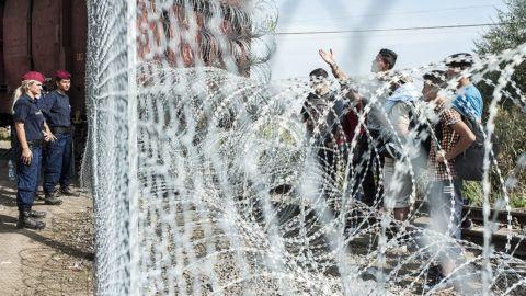 Röszke, 2015. szeptember 15.Migránsok a határ szerb oldalán a magyar oldalon álló rendőrnőkkel szemben a magyar-szerb határon, Röszke térségében 2015. szeptember 15-én. Ezen a napon hatályba léptek a migrációs helyzet miatti új szabályozások.MTI Fotó: Ujvári Sándor