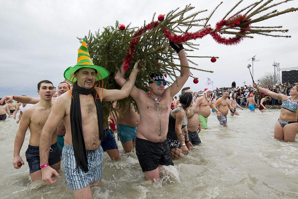 Szigliget, 2018. január 1.A december 24-én felállított karácsonyfát viszik ki a Balatonból a hetedik alkalommal megrendezett újévi csobbanás résztvevői a szigligeti strandon 2018. január 1-jén.MTI Fotó: Varga György