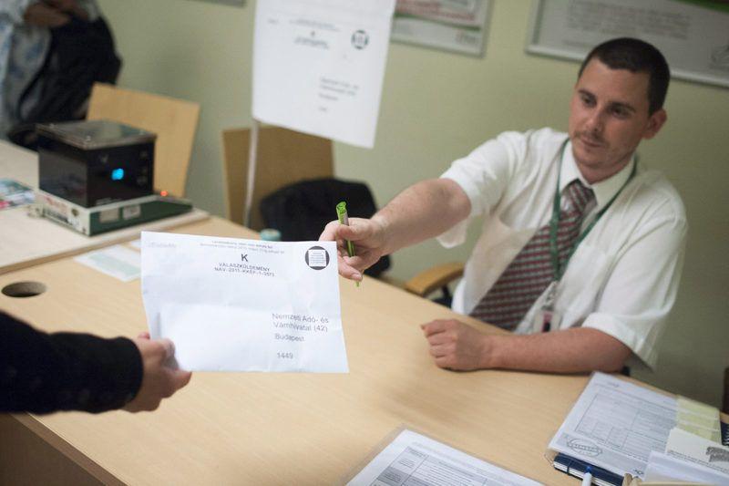 Budapest, 2013. május 21.Egy alkalmazott átvesz egy adóbevallást tartalmazó borítékot a budapesti Mammut I. bevásárlóközpont postahivatalában lévő külön pultnál 2013. május 21-én. A mai napon éjfélig lehet benyújtani a személyi jövedelemadó-bevallásokat a tavalyi évről.MTI Fotó: Marjai János