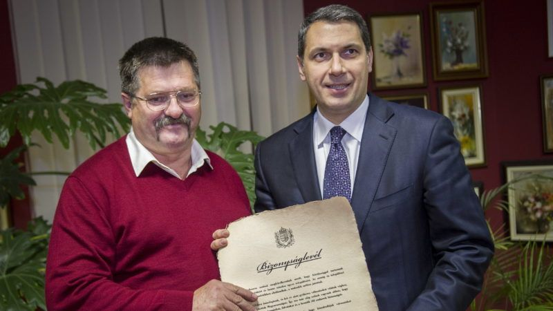 Csanádpalota, 2013. november 14. Lázár János, a Miniszterelnökséget vezetõ államtitkár, a térség országgyûlési képviselõje (j) átadja Kovács Sándornak, a Csongrád megyei Csanádpalota független polgármesternek az Orbán Viktor miniszterelnök által aláírt bizonyságlevelet a városházán 2013. november 14-én. A bizonyságlevél azt tanúsítja, hogy a kormány átvállalta a település adósságát, amely 67.5 millió forint volt. MTI Fotó: Rosta Tibor