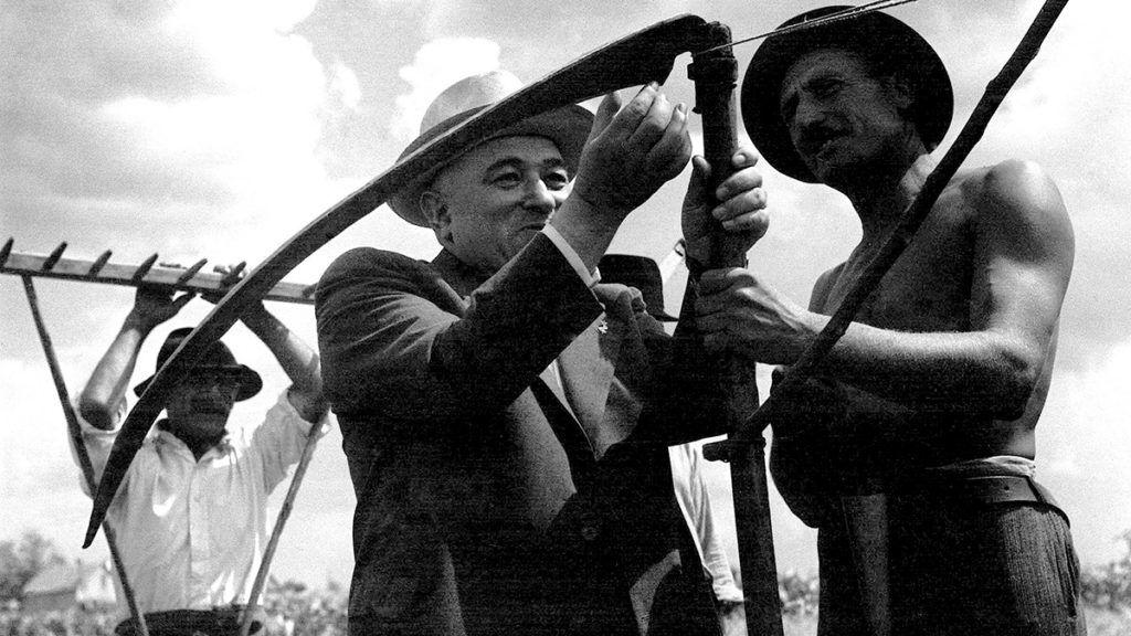 Bácsalmás, 1947. június 29.Rákosi Mátyás államminiszter, a magyar Kommunista Párt (MKP) főtitkára egy félmeztelen, kalapos parasztember kézi kaszájának élét vizsgálja a bácsalmási aratóünnepen. A háttérben egy másik, ingujjas dolgozó paraszt látható, aki a gereblyére támaszkodik.MTI Fotó/MAFIRT: Rév Miklós