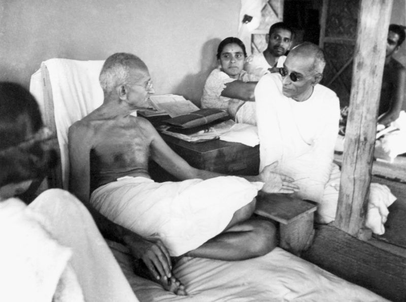 Indian statesman and activist Mohandas Karamchand Gandhi (1869 - 1948) talking with Chakraborty Rajagopalachari in his hut at Sevagram Ashram, 1942. (Photo by Dinodia Photos/Getty Images)