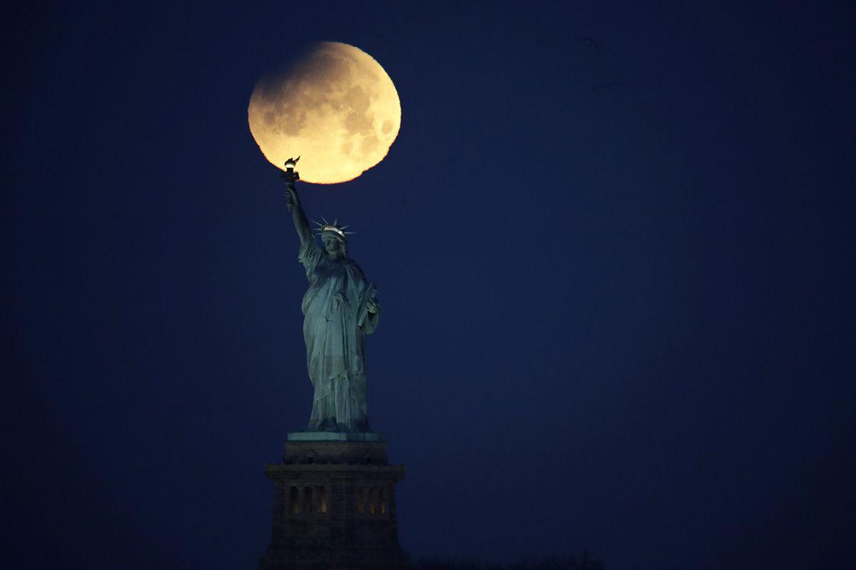 New York, 2018. január 31. Közeli telihold, úgynevezett szuperhold a New York-i Szabadság-szobor felett 2018. január 31-én. A szuperhold kifejezés az ellipszis alakú holdpálya Földhöz legközelebbi pontján bekövetkező telihold fázist jelöli, amikor az égitest a pályájának legtávolabbi pontjához képest nagyjából ötvenezer kilométerrel közelebb van a Földhöz, ezért az átlagosnál mintegy 14 százalékkal nagyobbnak látszik. (MTI/AP/Julio Cortez)