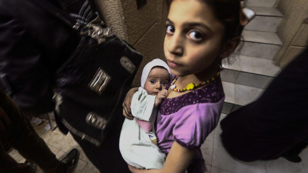 Duma, 2017. május 24. Szíriai kislány várja, hogy a Szíriai Arab Vörös Félhold humanitárius segélyszervezet munkatársa kanyaró és gyermekbénulás elleni szérummal oltsa be csecsemõkorú testvérét a szíriai fõváros, Damaszkusz közelében fekvõ Dumában 2017. május 24-én. A száz önkéntes részvételével elsõ alkalommal megtartott megelõzõ kampány keretében a városban 12 809 öt éven aluli gyermek részesült védõoltásban. (MTI/EPA/Mohamed Badra)