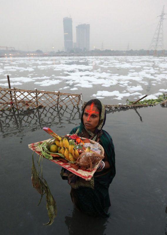 Újdelhi, 2018. január 9.A 2018. január 9-én közreadott képen a Jamuna folyó vegyszerhabbal borított vizében áll egy felajánlást tevő indiai nő a Csat Púdzsa hindu ünnep alkalmából Újdelhiben 2017. október 26-án. A Himalája Jamunotri-gleccserének kristálytiszta olvadékvizéből eredő folyó az indiai fővároson keresztül Uttar Prades szövetségi államban ömlik a Gangeszbe. Mindkét folyót vallásos tisztelet övezi, mivel a hinduk hite szerint a szent vizekben való megmártózás megszabadít a halál gyötrelmeitől. (MTI/EPA/Haris Tjagi)