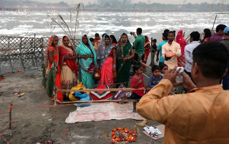 Újdelhi, 2018. január 9.A 2018. január 9-én közreadott képen a vegyszerhabbal borított Jamuna folyó partján fényképezkednek indiaiak a Csat Púdzsa hindu ünnep alkalmából Újdelhiben 2017. október 26-án. A Himalája Jamunotri-gleccserének kristálytiszta olvadékvizéből eredő folyó az indiai fővároson keresztül Uttar Prades szövetségi államban ömlik a Gangeszbe. Mindkét folyót vallásos tisztelet övezi, mivel a hinduk hite szerint a szent vizekben való megmártózás megszabadít a halál gyötrelmeitől. (MTI/EPA/Haris Tjagi)